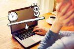 パソコンの上にある時計とドルのイラストを眺める人