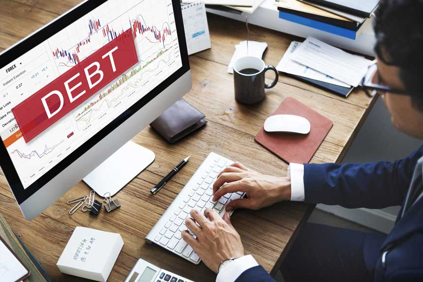 PCでFXのトレードをするビジネスマンと画面に映し出されるDEBTの文字