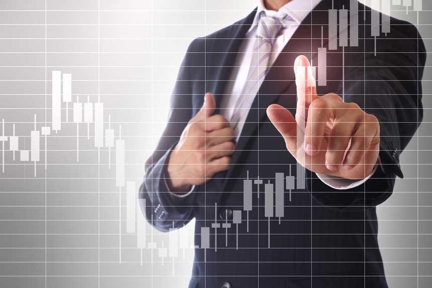 チャートに触れるビジネスマンと発光する指先