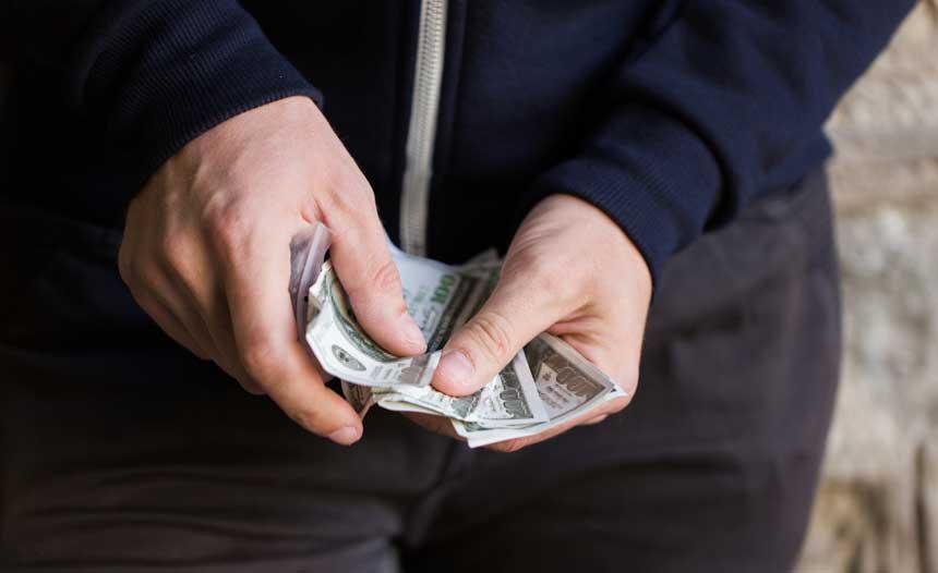 ドル札を数える男性