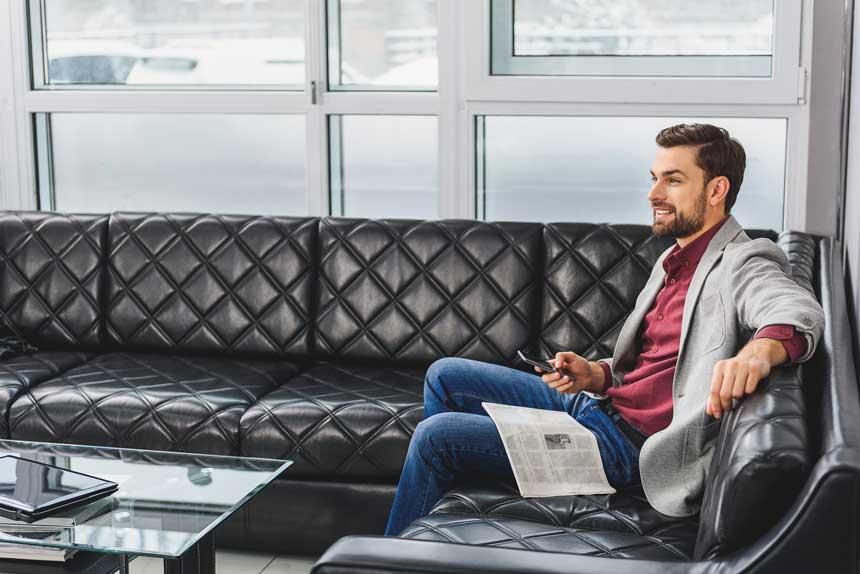 笑顔でソファーに座る男性
