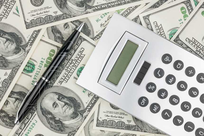 ドル札の上にあるペンと計算機