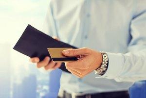 財布からクレジットカードを出す男性