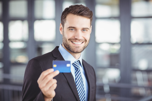 Close-up portrait of happy businessman showing credit card