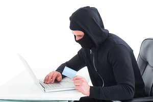 Hacker using laptop and credit card on white background