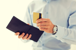 close up of man holding wallet and credit card